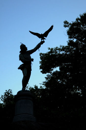 Low angle view of silhouette statue against clear sky