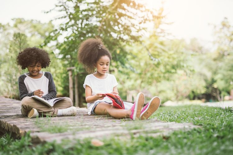 Children reading African African American Children Friends Grass Happiness Learning Read Reading USA Wisdom Book Boys Cheerful Child Childhood Education Enjoyment Friendship Girl Leisure Activity Outdoors Reading A Book Relaxation Studying
