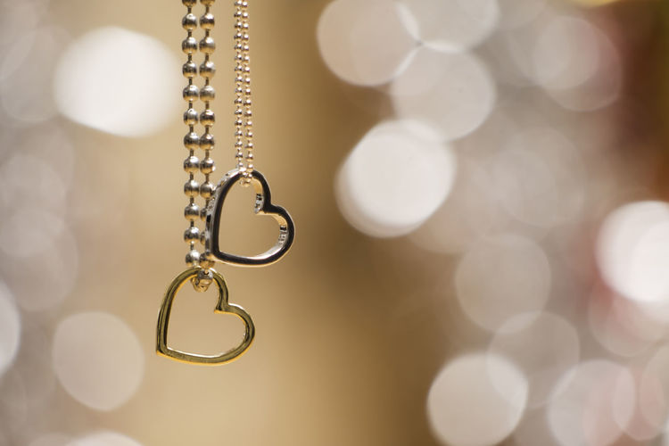 two heart pendants with necklace in soft and blur background Gold Love Lovers Necklaces Relationship Sign Bokeh Brilliant Close-up Couples Decoration Elégance Gift Glittering Gold Heart Heart Pendant Heart Shape Husband And Wife Jewelry Luxury Necklace Present Symbol Two Hearts