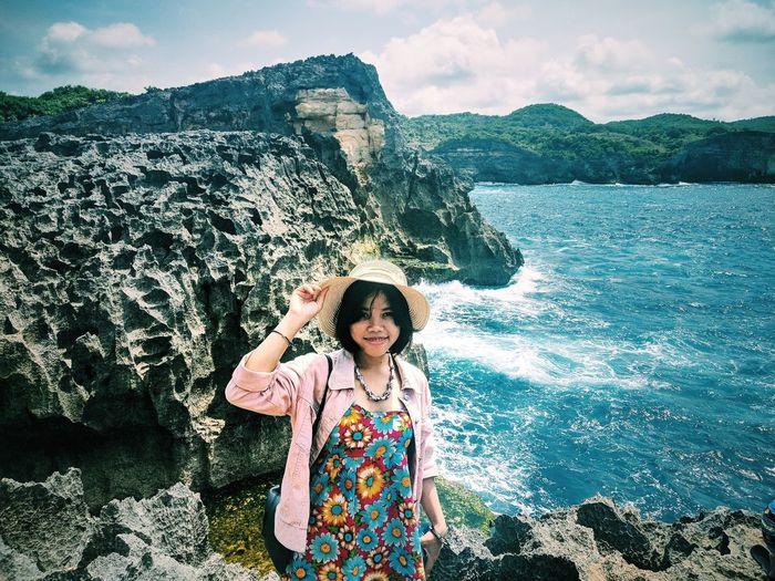 Portrait of woman standing on rock by sea