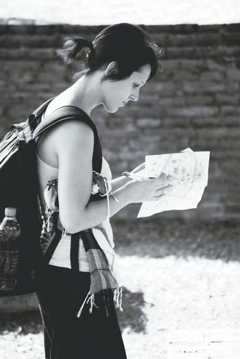 Side view of young woman holding maps while standing on field