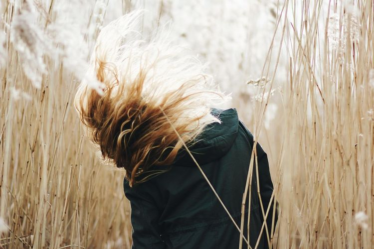 Rear view of woman tossing hair by plants