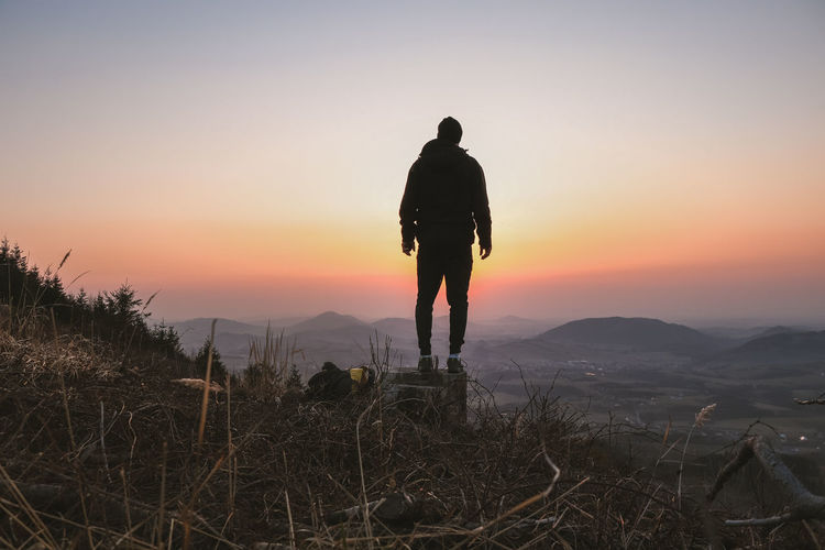 Rear view of silhouette man standing on mountain against sky during sunset