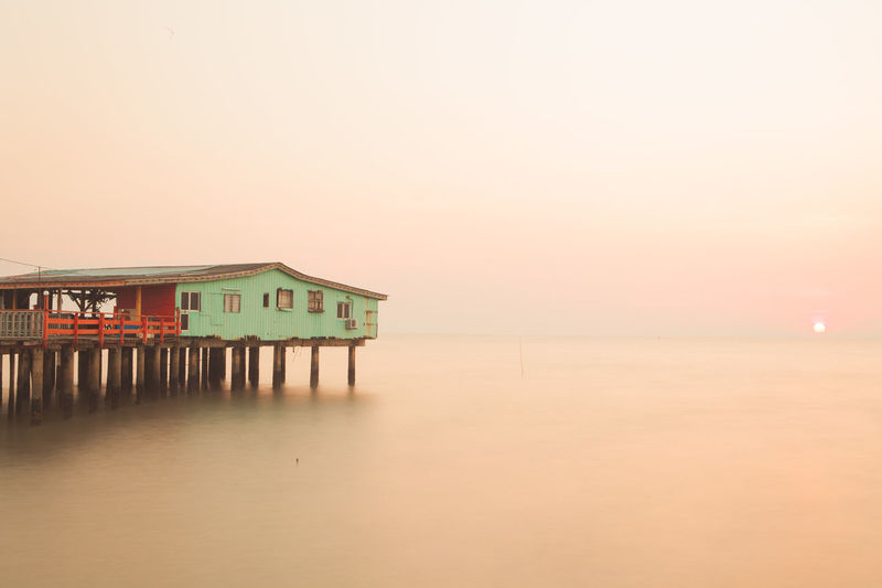 Stilt house by sea against clear sky during sunset