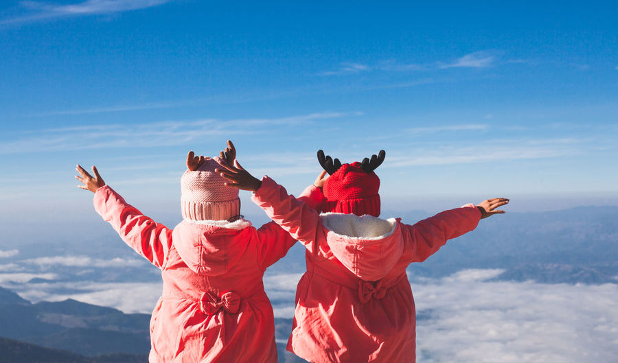 Rear view of siblings with arms outstretched standing against sky