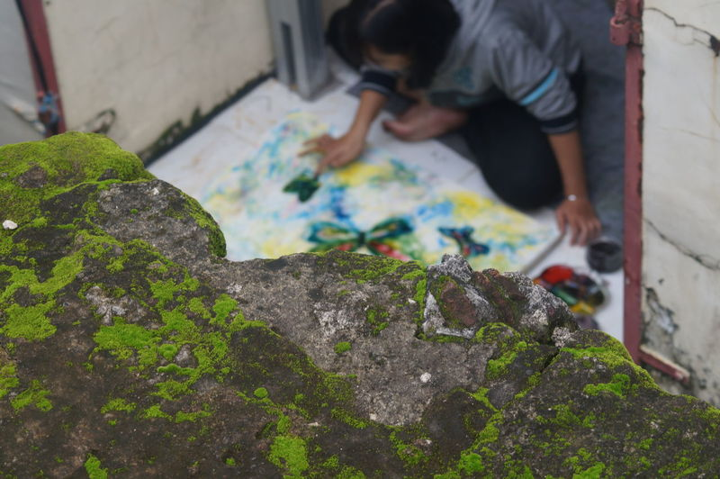 Moss covered wall against woman making rangoli on doorway