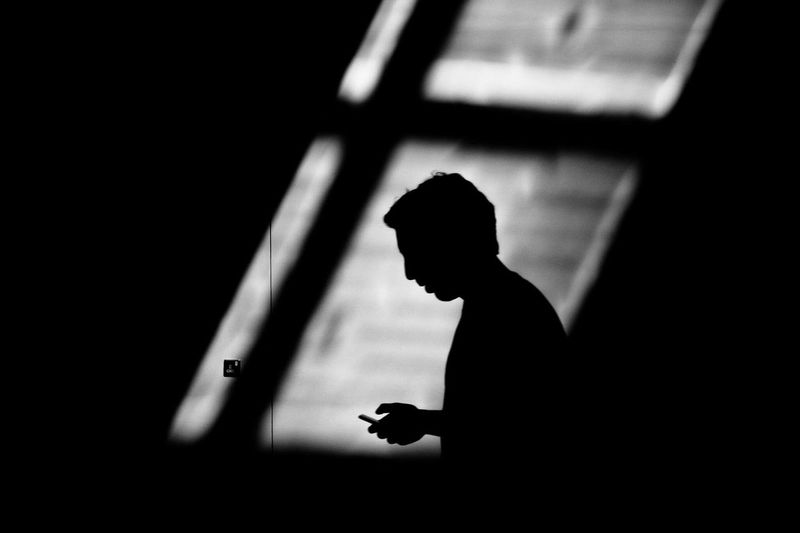 Silhouette of man using mobile phone