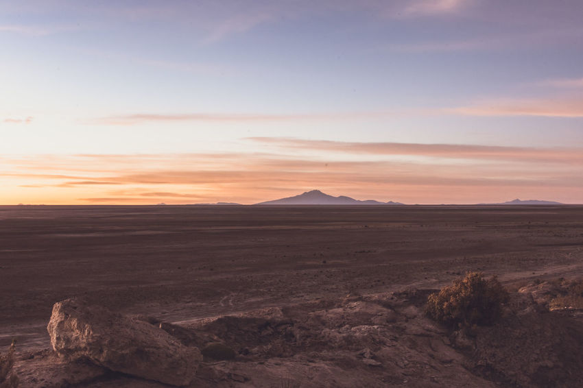 Sunset on The Edge of The Bolivian Salt Flats in Uyuni Attacama Bolivia Colchani Desert Dusk Golden Hour High Altitude Mountain Range Mountains Mountains And Sky Orange Paradise Salt Flats Salt Hotel Sunset Uyuni Vacation Wonders Of The World