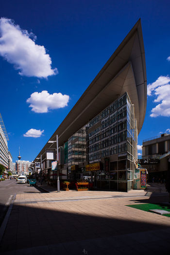 Road by buildings against blue sky in city