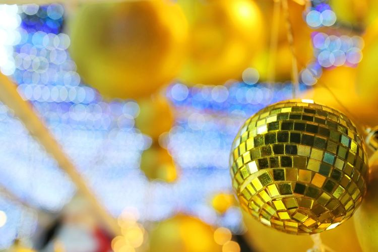 Christmas bokeh background. Lighting of christmas celebration with shiny golden ball, low key. Holiday background concept. Bokeh Lights X Mas  Golden Ball Cactus Bokeh Background Christmas Decoration Sphere Close-up Celebration Focus On Foreground Shiny Multi Colored Selective Focus Hanging Shape Event Disco Ball Indoors  Design Yellow Nightlife Party Joyful Happy New Year Crystal