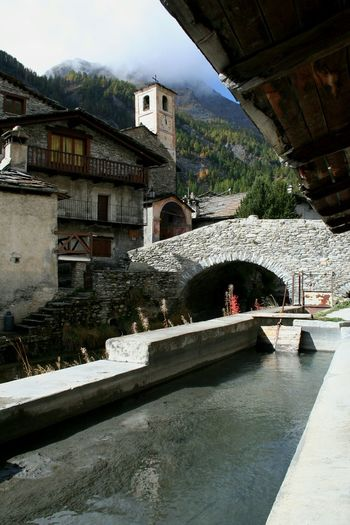 Architecture Building Exterior Built Structure Outdoors Travel Destinations Day No People Tree Bridge - Man Made Structure Sky Water Italian Alps Village Chianale Stone Building Mountain Village Old Church Old Architecture Bell Tower Peace And Tranquility Water Reflections Fountain Freshness Fresh Water Pure Water EyeEmNewHere