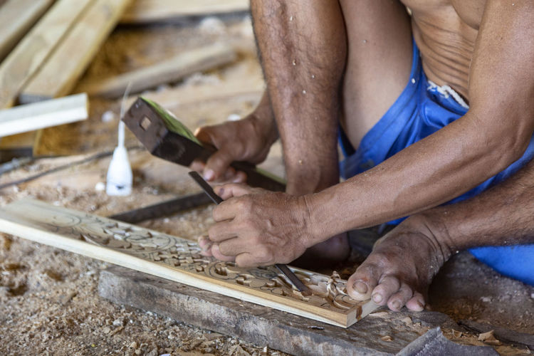 Isolated hands chiseling on the ground of a wood working shop in Nuda Penida, Indonesia. Asian  Bali Carver INDONESIA Indonesian Isolated Man Tradition Travel Wood Workshop Art Balinese Carving Chisel Culture Handmade Mallet Men Nusa Penida Sculptor Sculpture Southeast Asia Souvenir Traditional