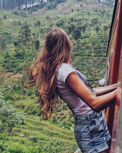 Woman peeking from train against mountain