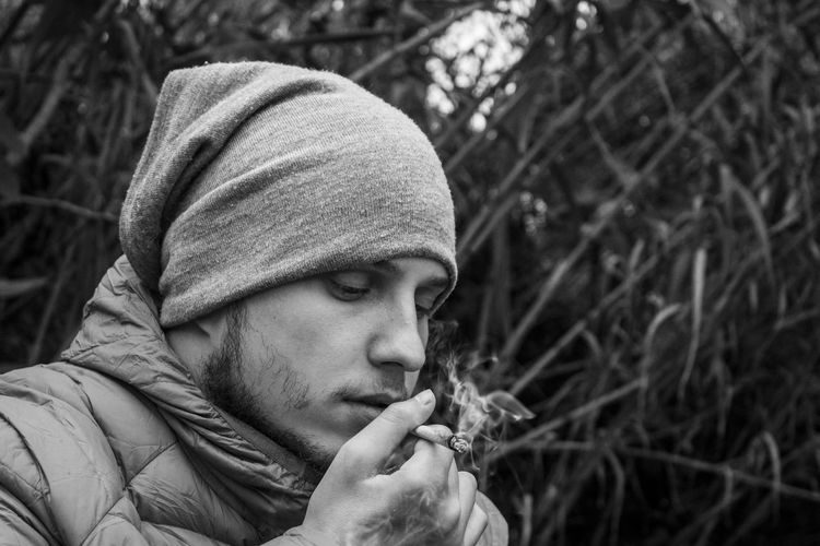 Man Smoking Marijuna Against Plants