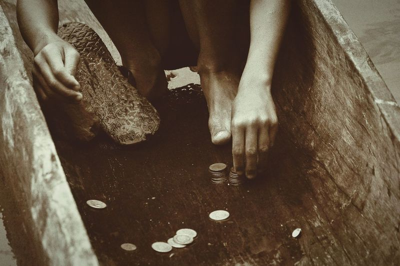 Low section of man stacking coins outdoors