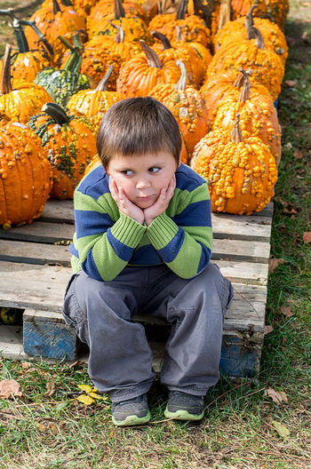 Thoughtful boy sitting with pumpkins on wooden floor