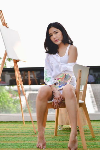 Low angle portrait of young woman holding palette while sitting on chair against clear sky
