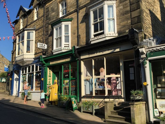 The fish and chip shop Pateley Bridge Yellow Fisherman FISH AND CHIP SHOP Architecture Built Structure Building Exterior Building City Day Street Window Real People Women Incidental People Outdoors Sunlight