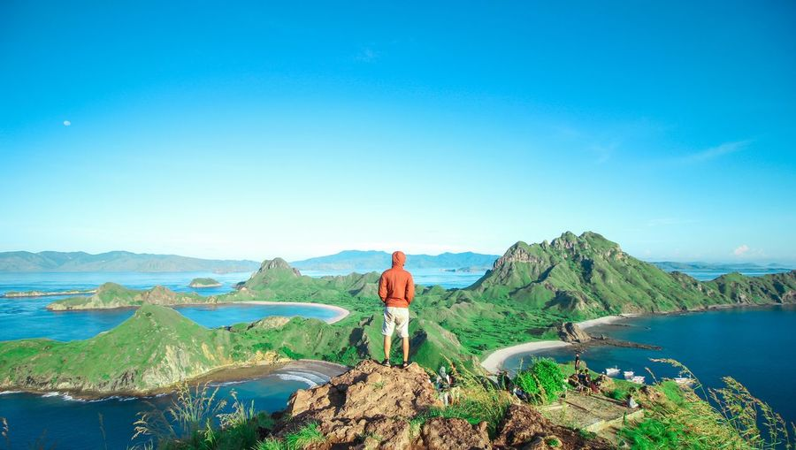 Rear View Of Man Standing On Mountain Against Clear Blue Sky
