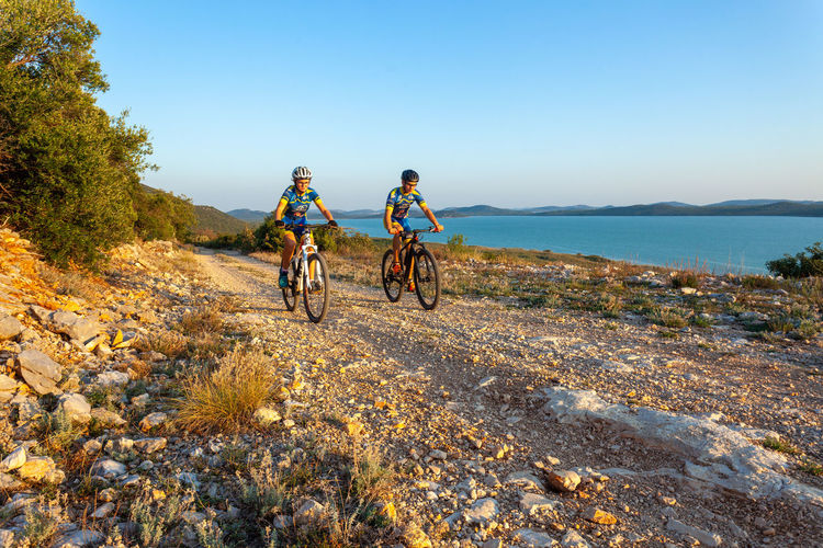 Men riding bicycle on shore against sky