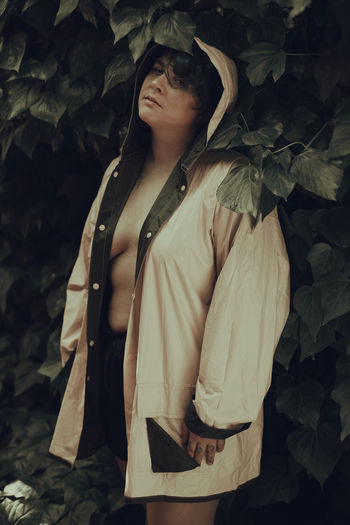 Midsection of woman standing against plants