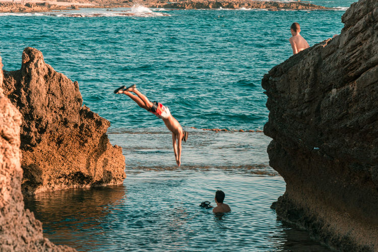 Man jumping on rock by sea
