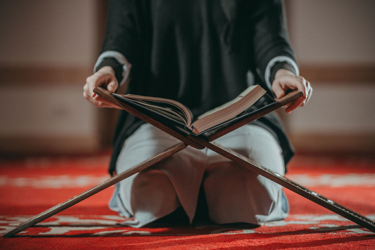 Midsection of woman reading koran while sitting on carpet