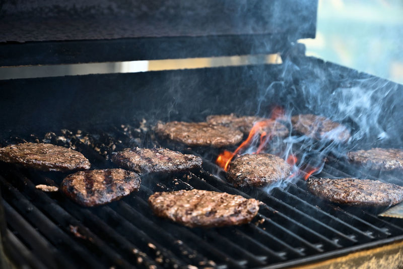 Grilling Hamburger Heat - Temperature Barbecue Food Barbecue Grill Preparation  Food And Drink Meat Burning Fire Grilled Fire - Natural Phenomenon Flame No People Smoke - Physical Structure Freshness Close-up Preparing Food Day Grate Red Meat Outdoors Beef Hamburger Snack
