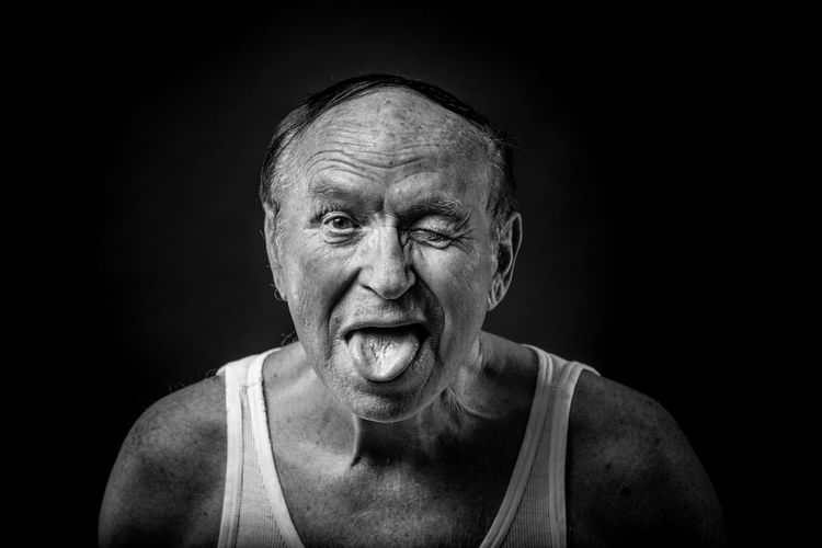 Portrait of man winking while sticking out tongue against black background