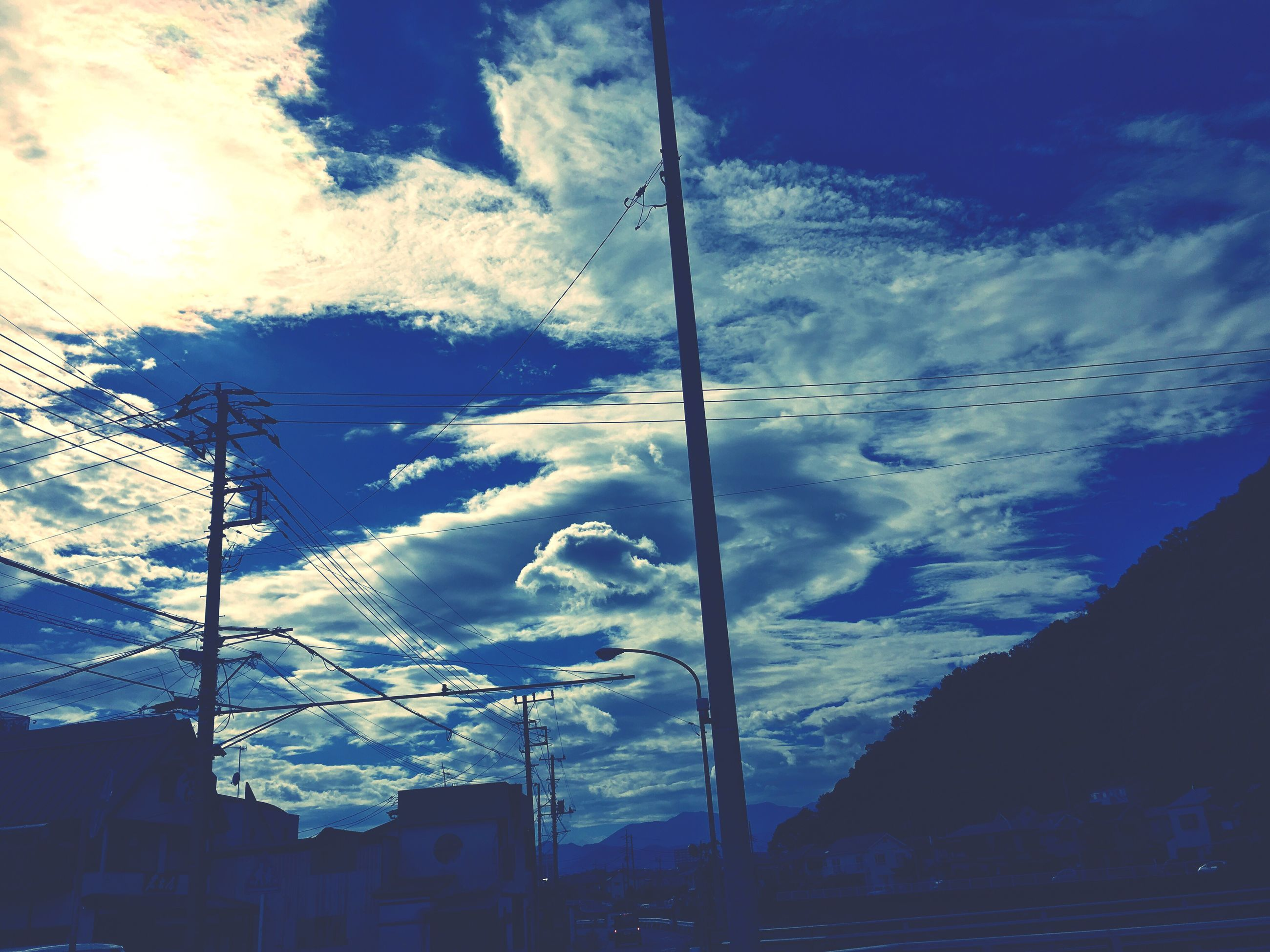 sky, cloud - sky, power line, low angle view, cloudy, street light, cloud, blue, cable, power supply, nature, weather, outdoors, no people, beauty in nature, pole, tranquility, scenics, day, tranquil scene, overcast