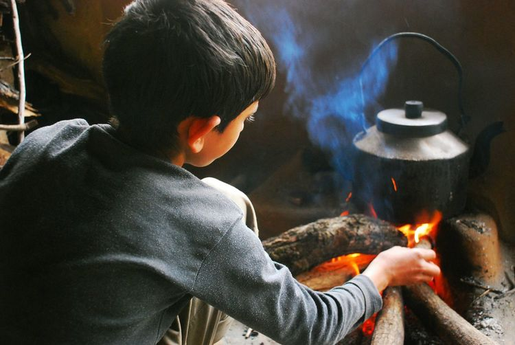 Boy Preparing Chai In Kettle On Fire