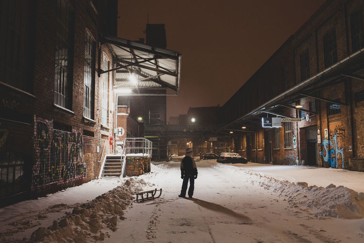 Rear view of person walking on snow covered street at night