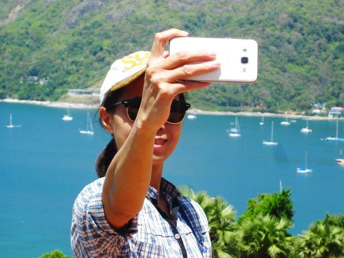 Woman Taking Selfie Against Sea