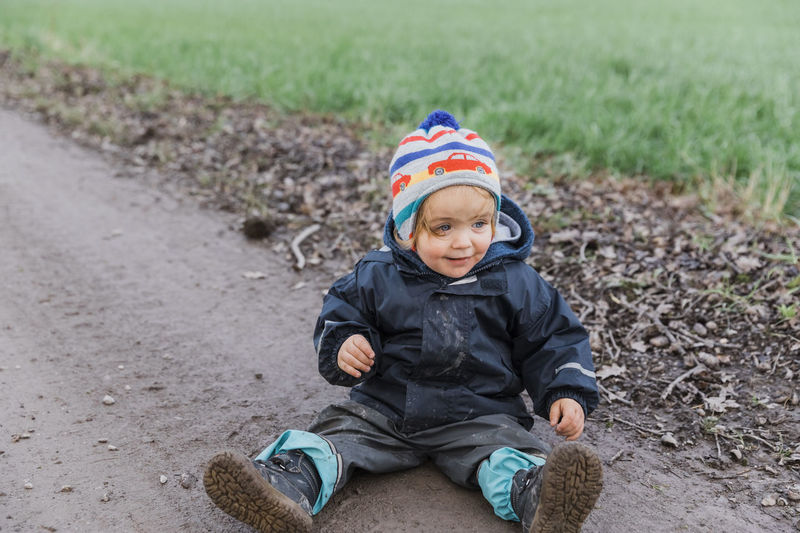 Happy toddler girl sitting with muddy pants on dirt road – Kempen, Germany Adventure Baby Boot Carefree Casual Caucasian Cheerful Child Childhood Close-up Coat Curiosity Cute Dirt Dirty Excitement Exploring Field Footpath Front View Full Length Fun Germany Girl Hand Happy Innocence Jacket Joy Land Looking Away Messy Mud Nature One Outdoors Pants People Playing Pointing Portrait Raincoat Road Sitting Smiling Toddler  Unhygienic Weather Wet Winter Males  Boys One Person Day Real People Clothing Warm Clothing Lifestyles