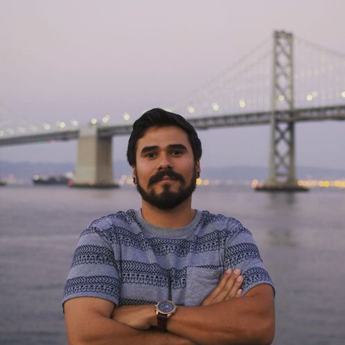Portrait of man with arms crossed standing against bay bridge