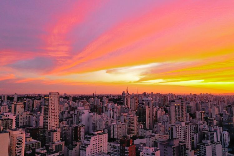 Aerial view of city against dramatic sky during sunset