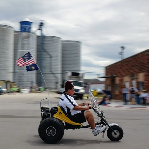 Village of Plymouth 125th Anniversary Celebration August 13, 2017 Plymouth, Nebraska American Life American Flag Americans Camera Work EventPhotography FUJIFILM X100S MidWest Motion Blur Nebraska Plymouth, Nebraska Small Town America Storytelling Summertime Architecture Building Exterior Built Structure City Cloud - Sky Day Elderly Man Flag Fujifilm_xseries Full Length Gocart Land Vehicle Men Mode Of Transport One Person Outdoors Parade Patriotism People Practicing Photography Real People Riding Road Shriners Sky Small Town Stories Speed Streetphotography Threewheeler Transportation Young Adult