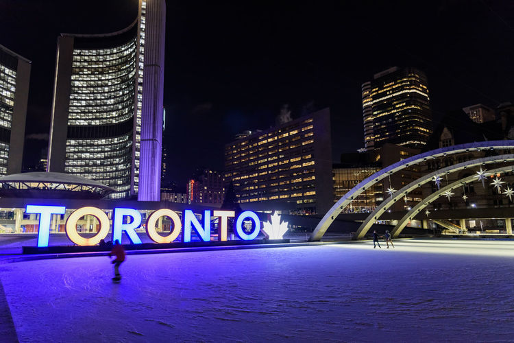 Night Illuminated Architecture Building Exterior City Built Structure Office Building Exterior Building Text Skyscraper Western Script City Life Outdoors Winter Sport Modern Sign Ice Rink Nature Sport Cityscape