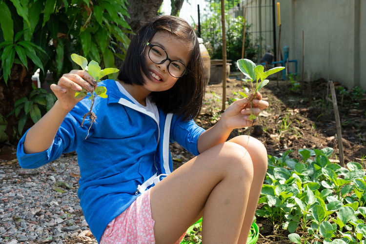 Portrait smiling girl holds the vegetable during harvesting from the planting garden at backyard