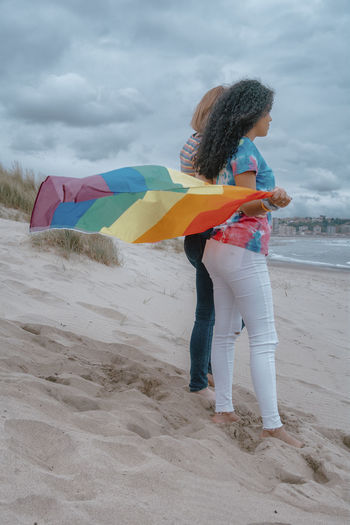 Woman with umbrella standing on beach