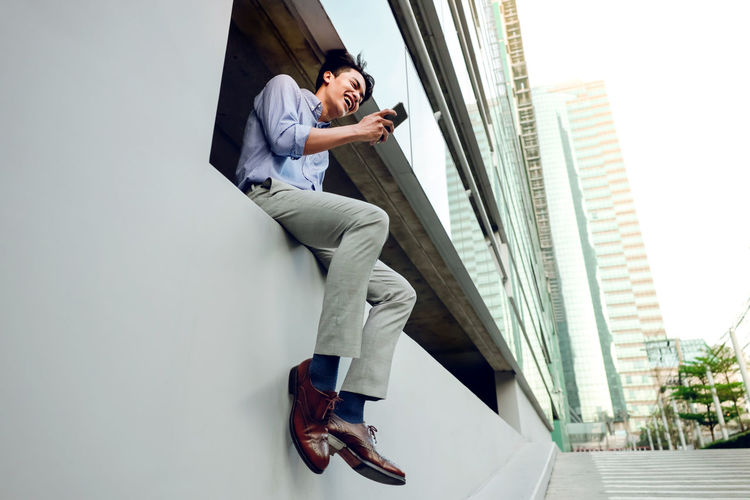 Low angle view of young man using phone in city