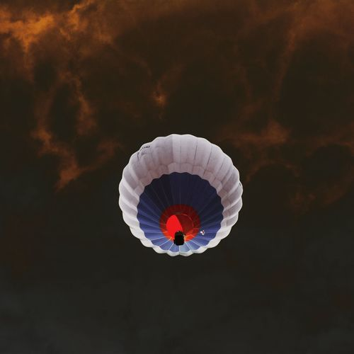 Low Angle View Of Hot Air Balloon Flying Against Cloudy Sky During Sunset