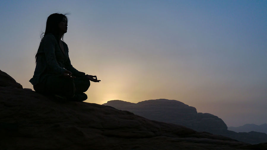 "A haven of peace. Sunrise in the Jordanian desert. (Panasonic DMC-GX1 LUMIX G 20/F1.7 ƒ/5.0 20mm 1/1000"" iso 160) 16:9 Beauty In Nature Calm Copy Space Desert Girl Jordan Landscape Landscapes With WhiteWall Lifestyles Meditation Nature Peace Scenics Silhouette Sunrise Tourism Tranquility Wadi Rum Working Www.benjaminvanderspek.com The KIOMI Collection Welcome To Black Long Goodbye"