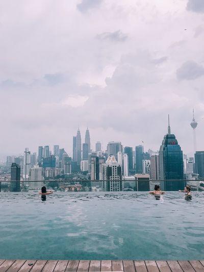People in infinity pool in city against sky