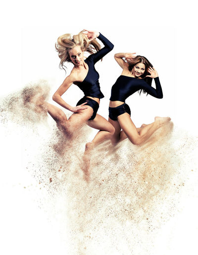 Two beautiful athletic girl jumping. Image with a digital effects Altered Art ArtWork Athletic Creative Digital Digital Art Digitally Generated Digitally Generated Image Fitness Generated Girls Graphic Graphical Jumping Looking At Camera Motion People Sandstorm Sexygirl Sport Sportive Studio Shot White Background Woman