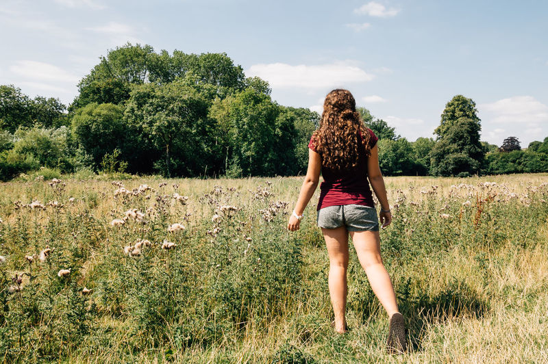 Young woman in the fields a sunny day of summer Beauty In Nature Casual Clothing Cloud Cloud - Sky Day Field Freedom Full Length Grass Grassy Green Color Growth Landscape Leisure Activity Lifestyles Nature Non-urban Scene Outdoors Scenics Sky Standing Tranquil Scene Tranquility Woman Young