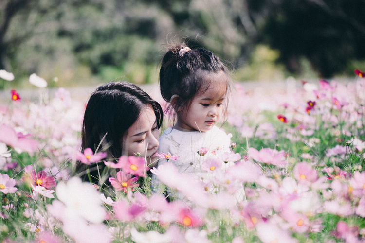 Rear view of mother and daughter on flowering plants