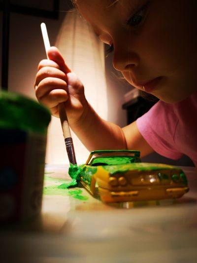 Close-up of cute mischievous girl painting toy car at home
