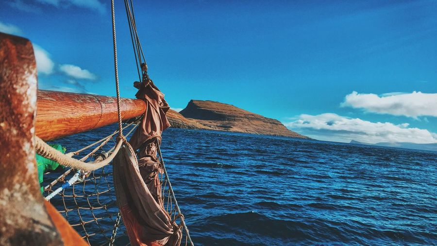 Cropped Image Of Boat Sailing In Sea With Mountain In Background