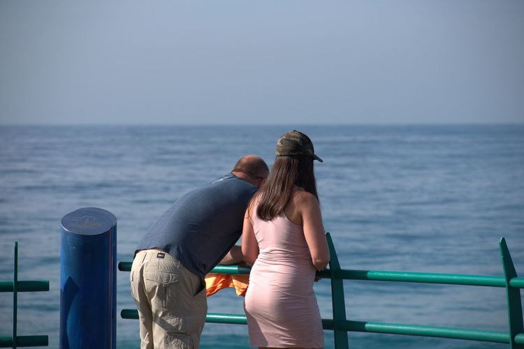 Rear view of couple looking at sea against clear sky
